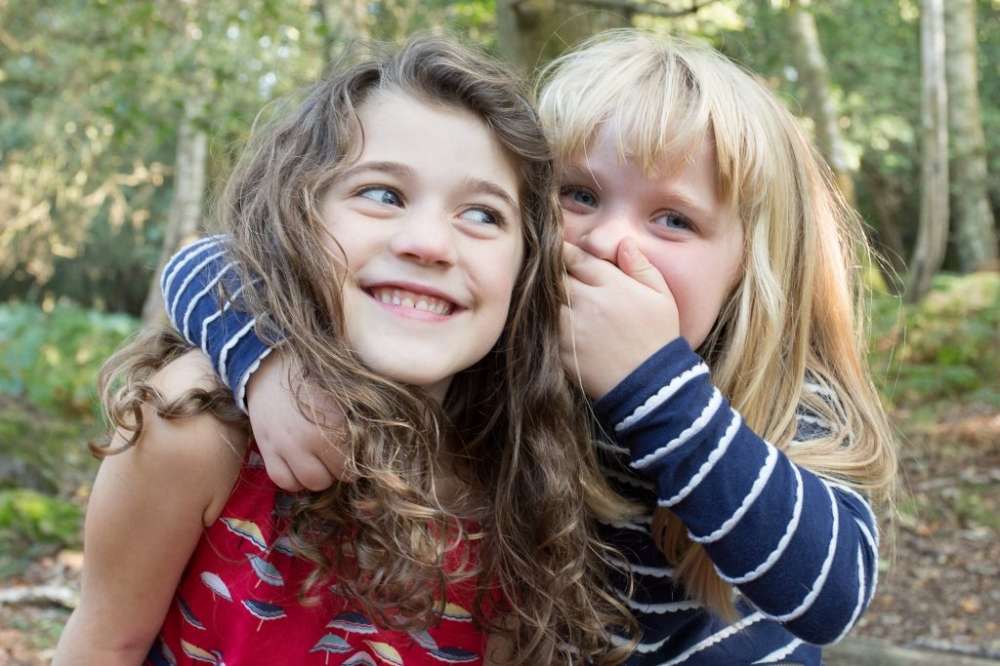 Two young sisters share a joke