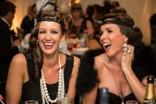 Two party guests in 1920s dress share a joke