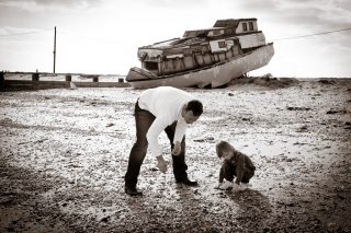Father and child look for shells on a beach with a derelict boat in the background