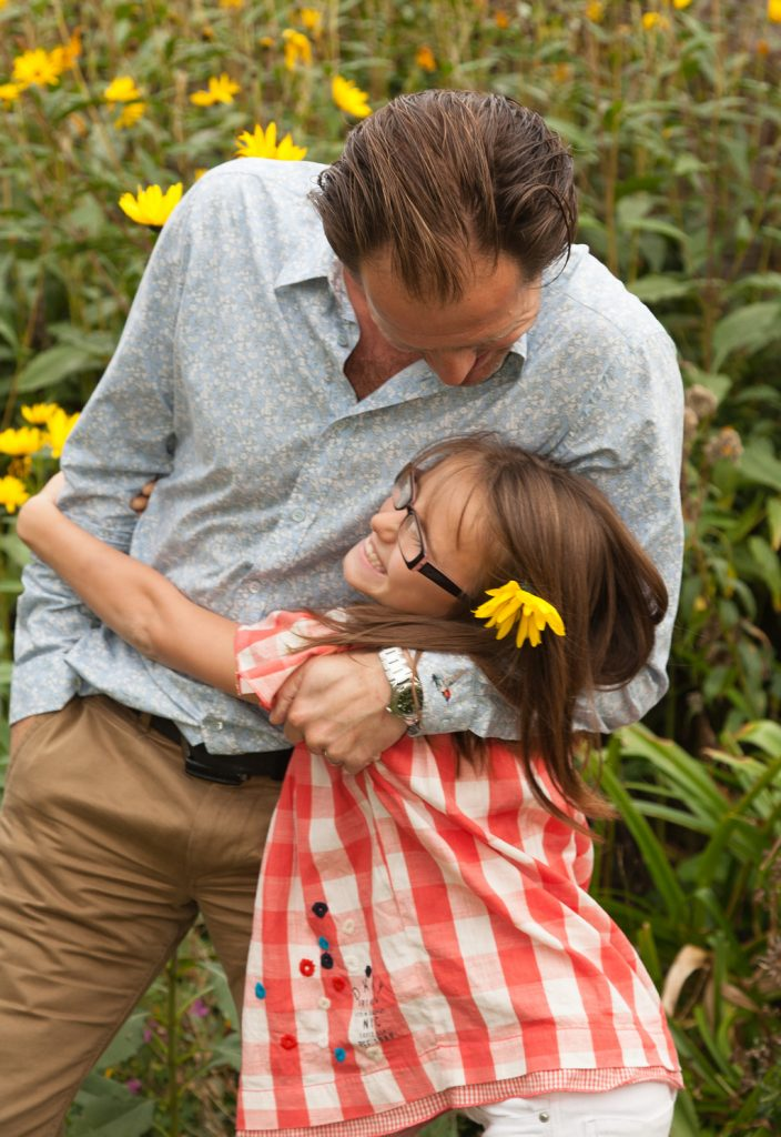 Father and daughter embrace in their garden
