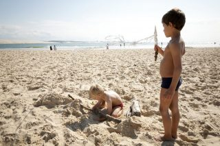 Two young boys play on the sand near the sea