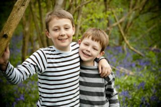 Brothers smile for the camera in bluebell wood