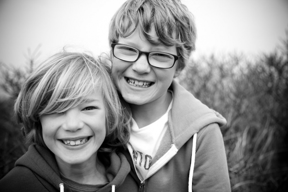Two young boys one with glasses, pose for the camera
