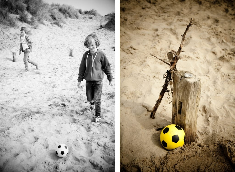 Two boys playing football in the sand dunes