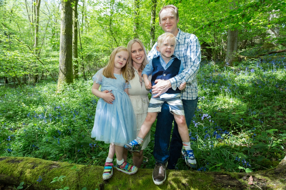 Happy family of four in bluebell woods.
