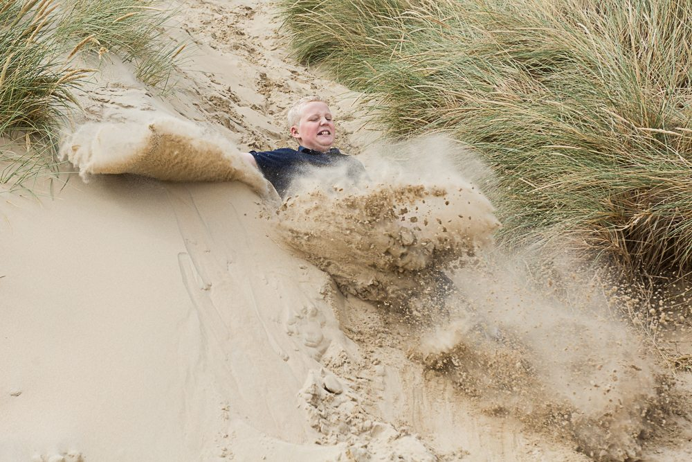 Young boy slides down a sand dune