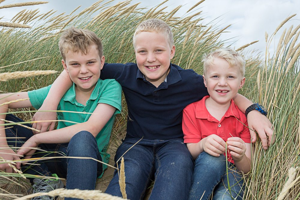 Three young boys sitting on a sand dune