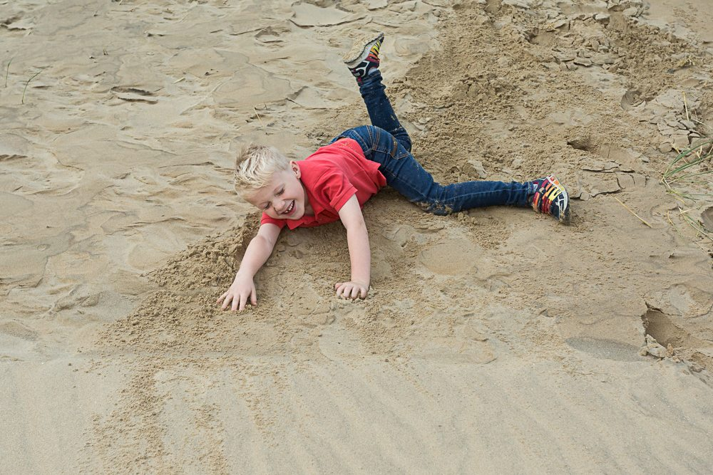 Young boy rolls in the sand