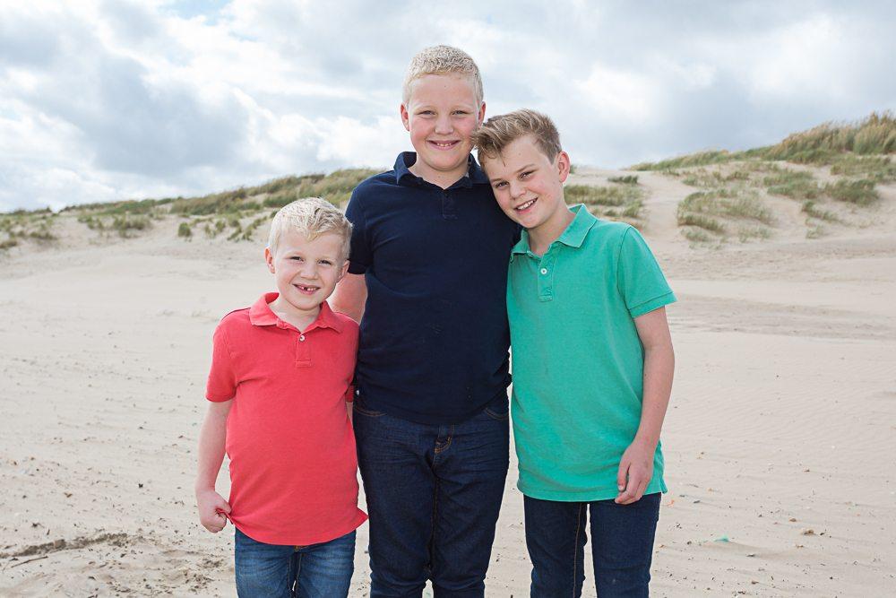 Three boys on an empty beach in Summer