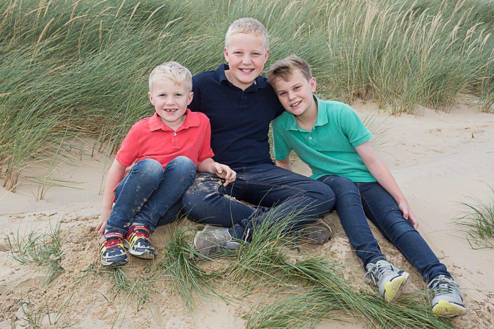 Three boys on beach pose for camera