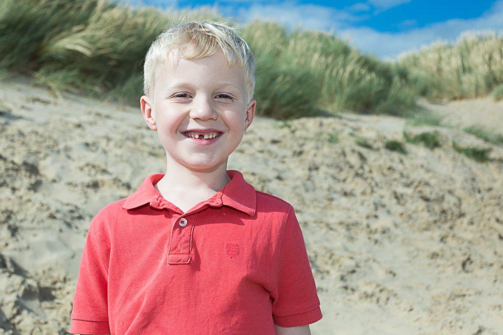 Boy on beach smiles at camera