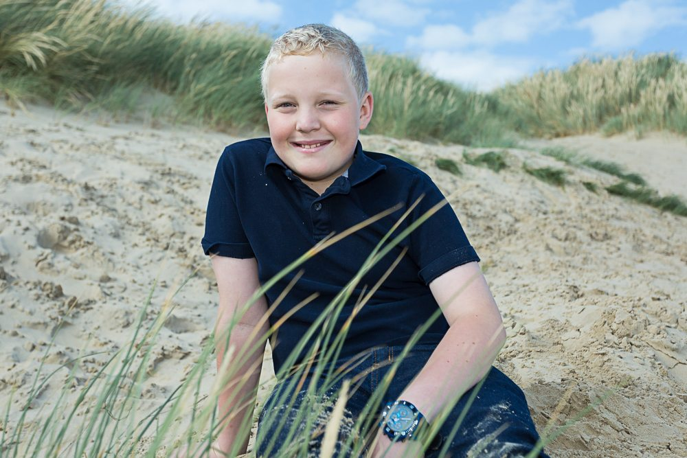 Young blonde boy poses for camera on beach
