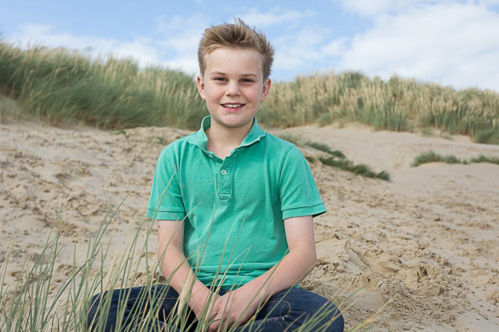 Young boy poses for camera on beach