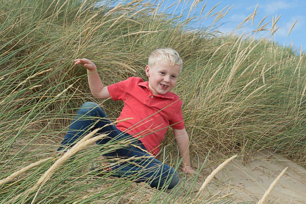 Young boy sits on a dune amongst marram grass