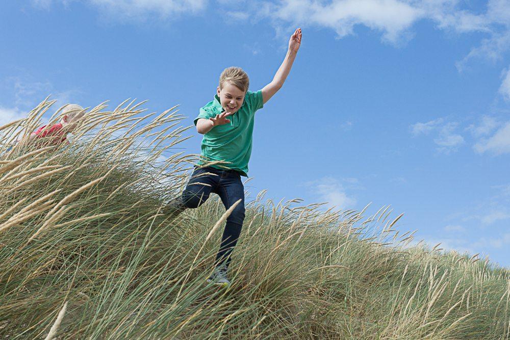 Boy jumping off a sand dune