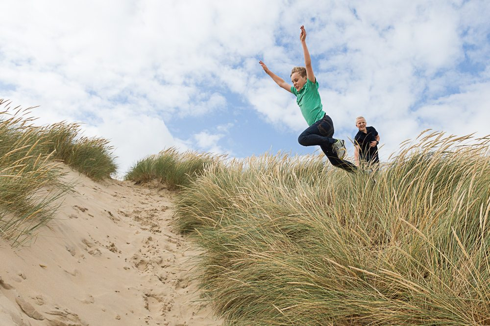 Two boys jumping from sand dunes