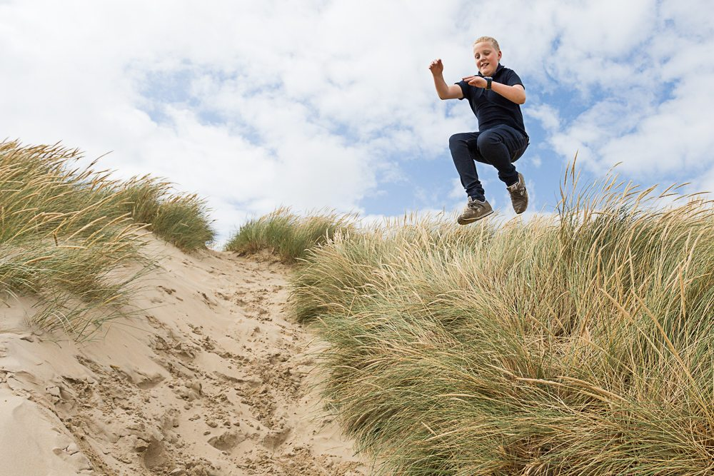 Young boy jumping off the top of a sand dune