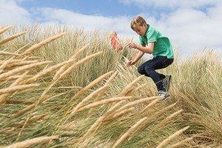 Young boy jumping through marram grass