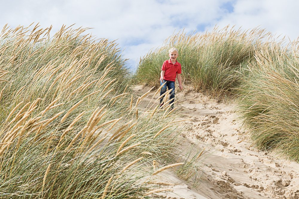Six year old boy stands at the top of a large sand dune