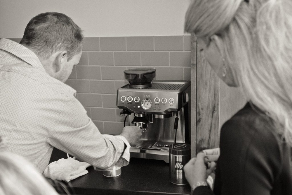 Wife looks on as her husband makes coffee