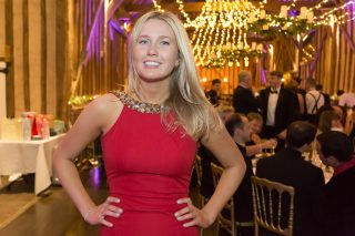 A young blonde haired lady in a red dress poses in front of a party scene