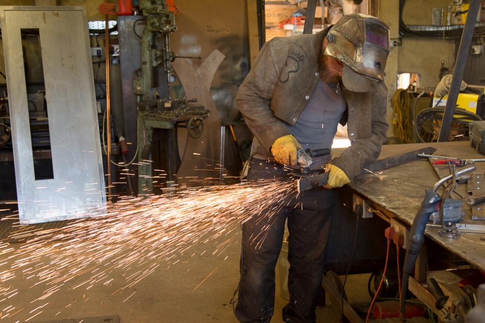 Welder using an angle grinder in a workshop, creating sparks