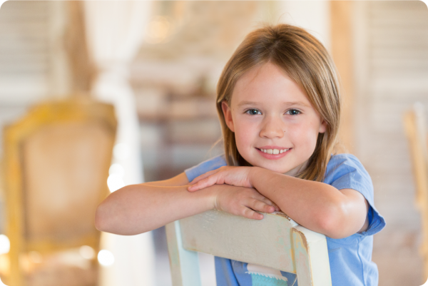 Young girl leans on a chair